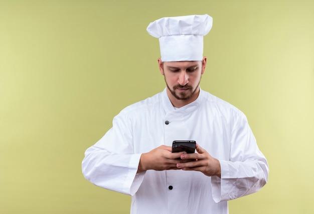 Chef profissional cozinheiro de uniforme branco e chapéu de cozinheiro segurando um smartphone, conversando com alguém em pé sobre um fundo verde