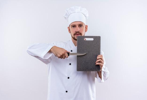 Chef profissional cozinheiro de uniforme branco e chapéu de cozinheiro segurando uma placa de corte e uma faca, parecendo confiante em pé sobre um fundo branco