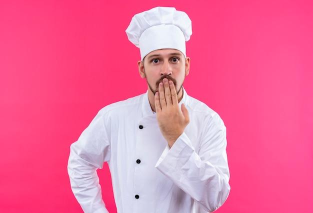 Chef profissional cozinheiro em uniforme branco e chapéu de cozinheiro parecendo espantado e surpreso, cobrindo a boca com a mão em pé sobre um fundo rosa