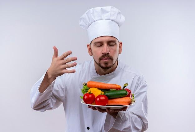 Chef profissional cozinheiro em uniforme branco e chapéu de cozinheiro segurando o prato com legumes e inala o cheiro deles em pé sobre um fundo branco