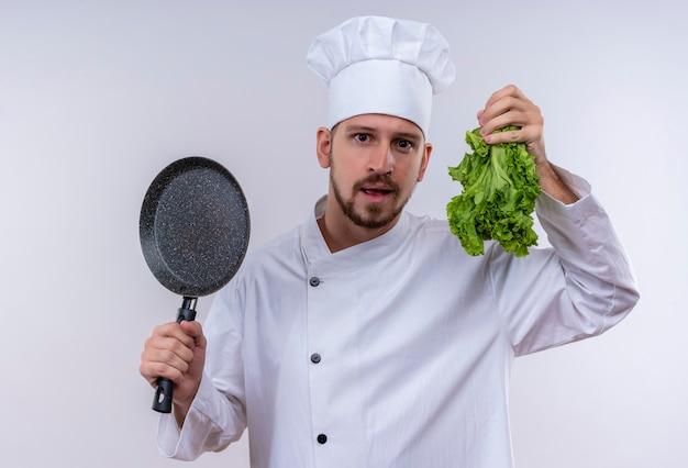 Chef profissional cozinheiro em uniforme branco e chapéu de cozinheiro segurando uma frigideira e alface fresca sorrindo em pé sobre um fundo branco