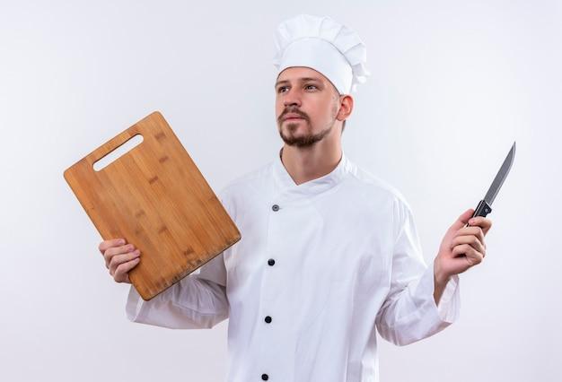 Chef profissional cozinheiro em uniforme branco e chapéu de cozinheiro segurando uma tábua de madeira e uma faca olhando para o lado com uma expressão pensativa no rosto em pé sobre um fundo branco