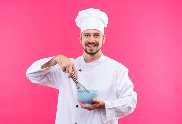 Chef profissional cozinheiro em uniforme branco e chapéu de cozinheiro segurando uma tigela, batendo algo com um batedor de arame sorrindo alegremente em pé sobre um fundo rosa
