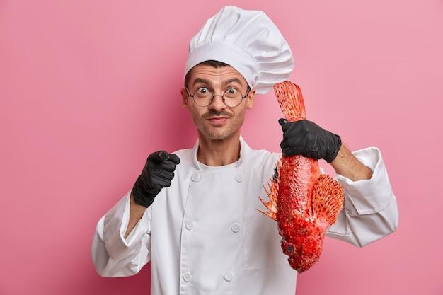 Chef profissional do sexo masculino segura grande peixe vermelho cru e sugere cozinhar uma refeição deliciosa para você