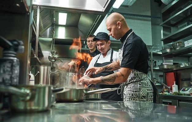 Chef profissional ensinando seus dois jovens estagiários a flambar alimentos com segurança. cozinha de restaurante