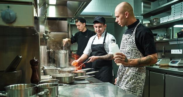 Chef profissional ensinando seus dois jovens estagiários a flambar alimentos com segurança. técnicas de cozinha