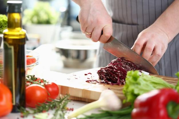Chef profissional mãos fatiar repolho roxo