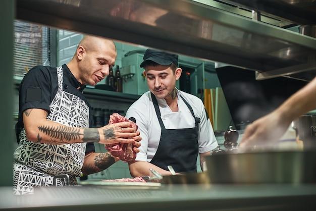 Chef profissional mostrando uma carne vermelha para seu assistente na cozinha de um restaurante