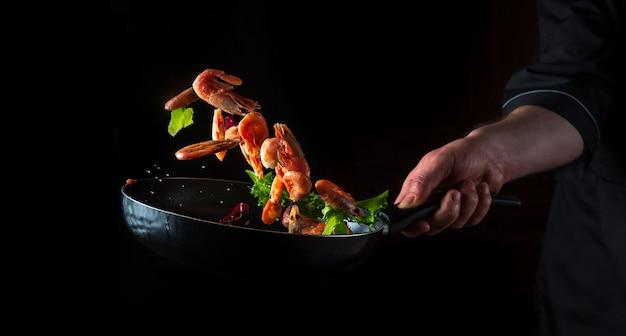 Chef profissional prepara camarão com ervas. cozinhar frutos do mar, comida vegetariana saudável e comida em um fundo escuro. espaço publicitário grátis