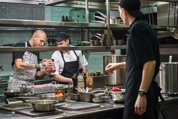 Chef profissional segurando uma carne vermelha e ensinando seus assistentes a escolhê-la para cozinhar