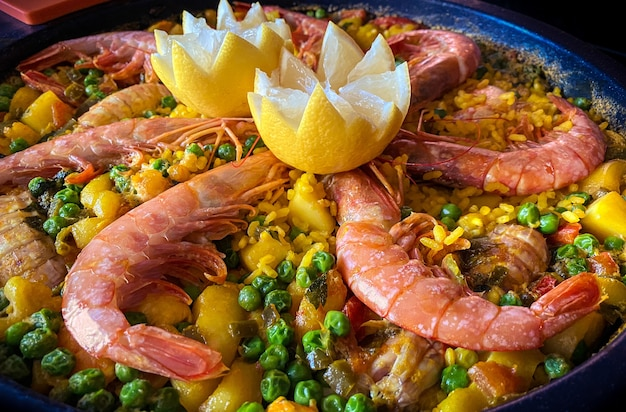 Chef que prepara uma paella borbulhando com camarão, limão e frutos do mar variados. preparando tapa comida típica espanhola deliciosa. saboroso prato da espanha