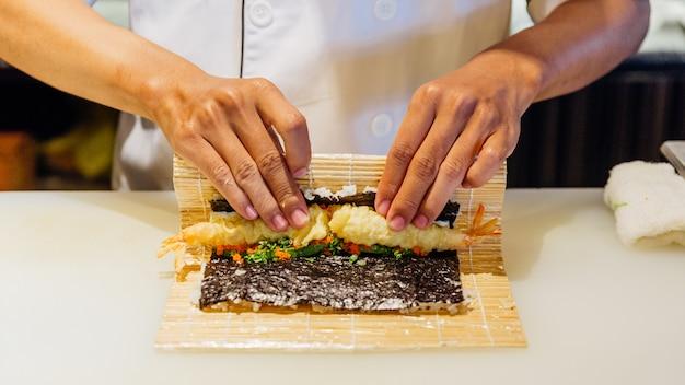 Chef rolando maki sushi com arroz, tempura de camarão, abacate e queijo dentro da farinha de tempura crocante coberta.