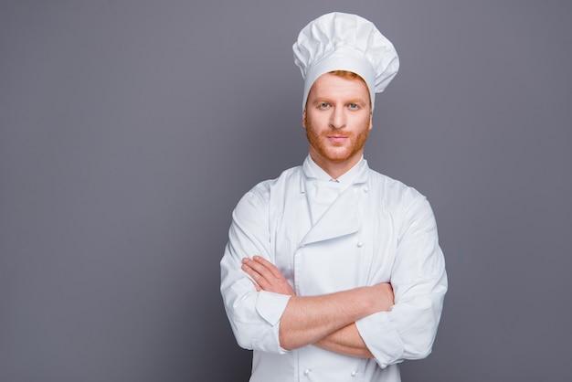 Chef ruivo de uniforme posando contra a parede cinza