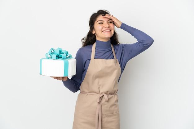Chef russo de confeitaria segurando um grande bolo isolado no fundo branco e sorrindo muito