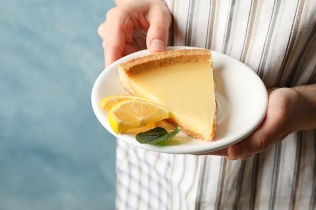 Chef, segurando a placa com limão torta fatia contra azul, close-up