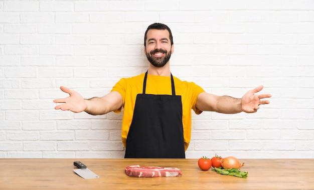 Chef segurando em uma cozinha apresentando e convidando para vir com a mão