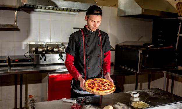 Chef segurando pizza nas mãos