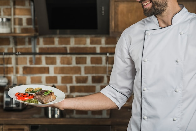 Chef segurando prato preparado para servir no restaurante