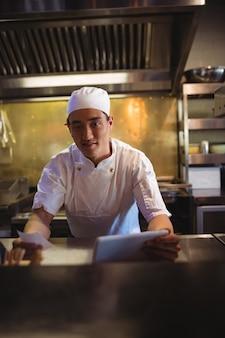 Chef segurando um tablet digital e uma lista de pedidos na cozinha