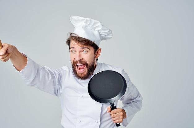 Chef segurando uma frigideira preparando comida em um restaurante de utensílios de cozinha