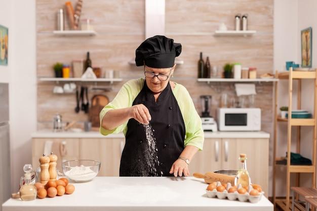 Chef sênior espalhando farinha com a mão para a preparação de alimentos na cozinha de casa usando avental