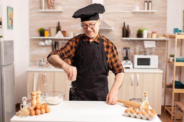 Chef sênior preparando pão caseiro polvilhando farinha de trigo na mesa da cozinha. chef sênior aposentado com bonete e avental, em uniforme de cozinha, polvilhando ingredientes peneirados com a mão.
