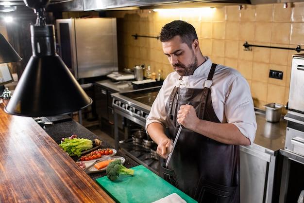 Chef sério e bonito com avental, afiar a faca e afiar enquanto se prepara para cozinhar na cozinha do restaurante