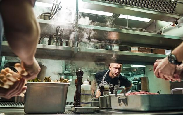 Chef sério está olhando como seus assistentes estão cozinhando uma carne na cozinha de um restaurante