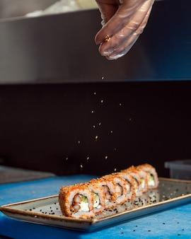 Chef servindo sementes de gergelim no rolo quente de sushi kani de perto