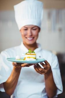 Chef sorridente, apresentando sua comida