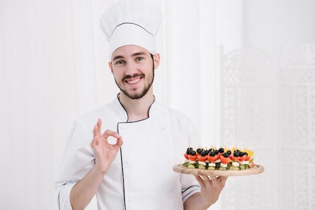 Chef sorridente com chapéu segurando placa