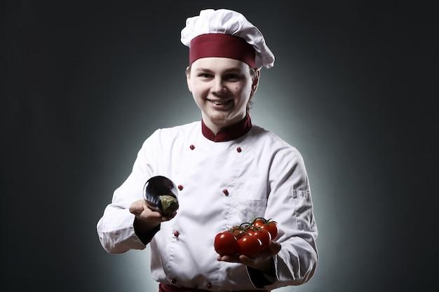 Chef sorridente com legumes