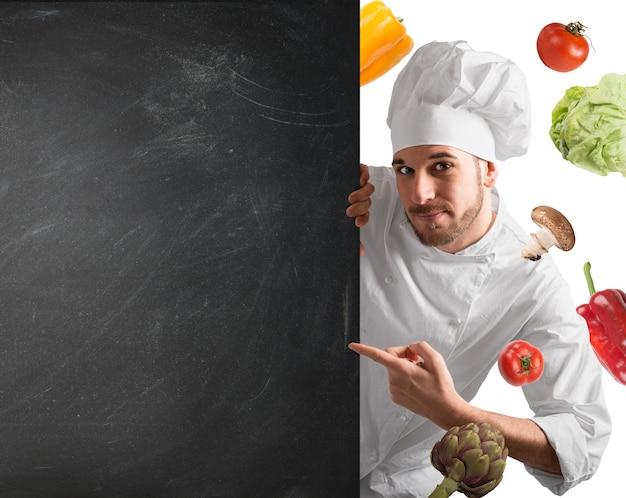 Chef sorridente com quadro-negro e vegetais