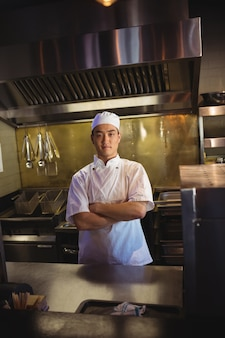 Chef sorridente em pé com os braços cruzados na cozinha comercial