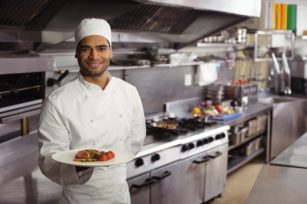 Chef sorridente segurando um prato delicioso na cozinha