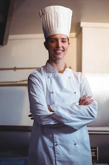 Chef, sorrindo e posando com braços cruzados