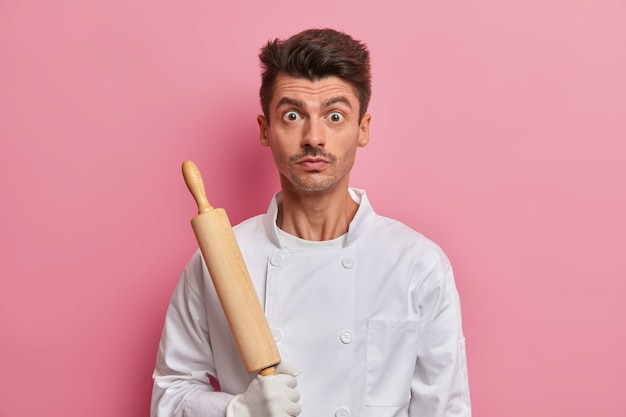 Chef surpreso com utensílio de cozinha, vestido de uniforme branco, padeiro ocupado segurando rolo de massa