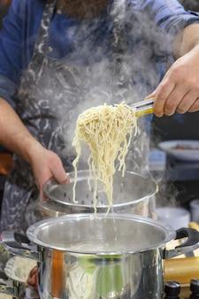 Chef tira com fenda de macarrão de ovo fumegante quente da panela