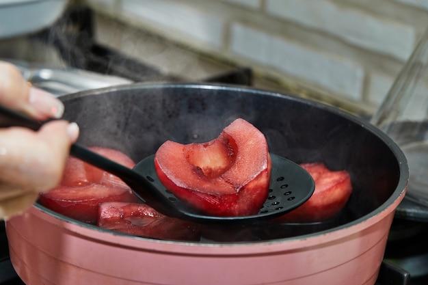 Chef tira peras prontas cozidas em calda vermelha com vinho no fogão a gás.