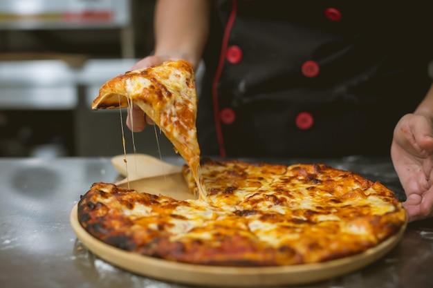 Chef tomando pizza na cozinha