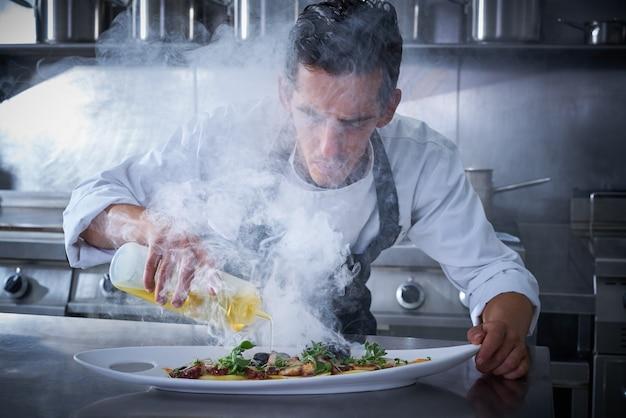 Chef trabalhando na cozinha com fumaça e óleo