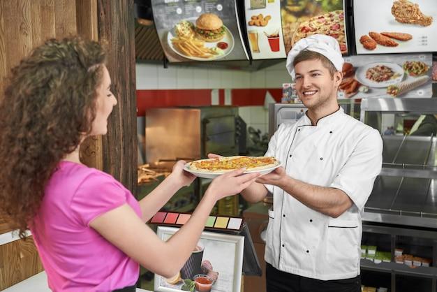Chef, trabalhando na pizzaria e propondo pizza a menina bonita.