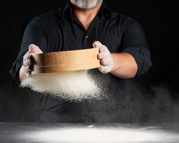 Chef, um homem de uniforme preto tem uma peneira redonda de madeira nas mãos e peneira farinha de trigo branca sobre um fundo preto, as partículas voam em direções diferentes, espaço empoeirado