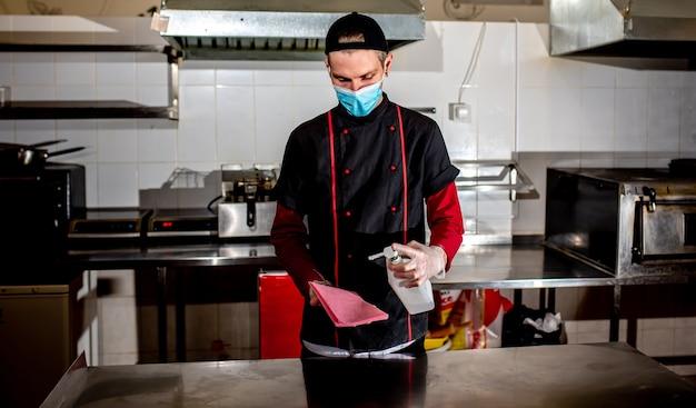 Chef usando máscara médica, desinfetando mesa de trabalho com anti-séptico
