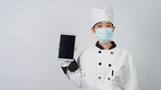 Chef usando máscara médica protetora de rosto ou respirador para proteção contra doenças virais. segurança alimentar e pandemia de coronavírus. chef posando de gesto representam pedidos on-line. saúde alimentar.