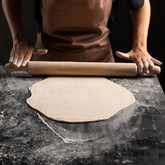 Chef usando rolo na massa