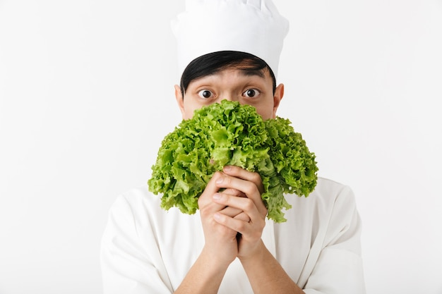 Chefe alegre asiático com uniforme branco de cozinheiro, sorrindo para a câmera enquanto segura uma salada de alface verde isolada na parede branca