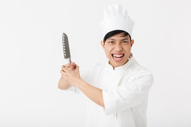 Chefe alegre asiático com uniforme de cozinheiro branco, sorrindo para a câmera enquanto segura uma faca grande isolada sobre a parede branca