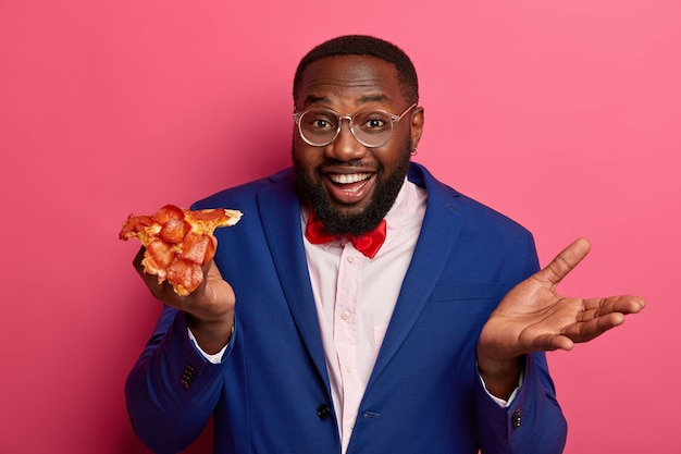 Chefe alegre faz um lanche depois do trabalho, segura uma pizza apetitosa, se veste formalmente, levanta a palma da mão, usa óculos, come fast food