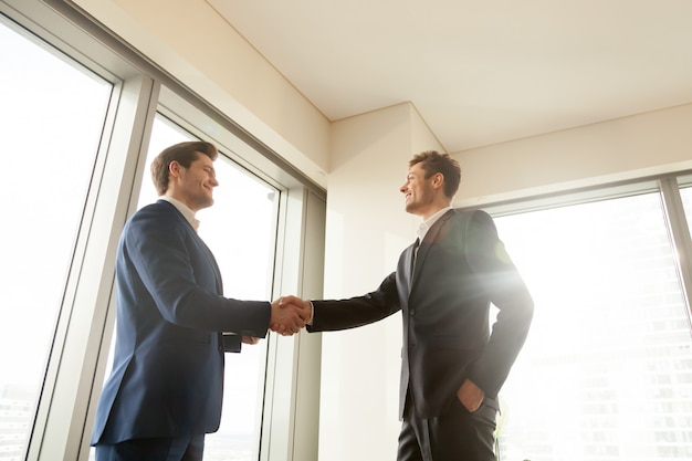 Chefe, apertando a mão e agradecendo o trabalhador pelo bom trabalho